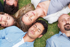 Group of people lying on grass taking a nap Stock Image