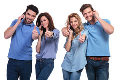 Group of  people making the ok  sign  on the phone. Casual group of young people making the ok thumbs up sign while talking on the phone Stock Images