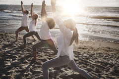 Group of people making yoga exercises on beach Royalty Free Stock Photography