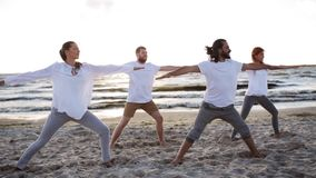 Group of people making yoga exercises on beach stock video footage