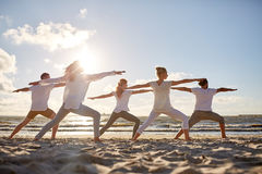 Group of people making yoga exercises on beach. Fitness, sport, yoga and healthy lifestyle concept - group of people making warrior pose on beach royalty free stock image
