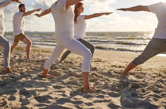 Group of people making yoga exercises on beach. Fitness, sport, yoga and healthy lifestyle concept - group of people making warrior pose on beach stock photos