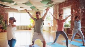Group of people making yoga exercises in gym stock footage