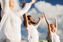 Group of people making yoga exercises outdoors stock photos