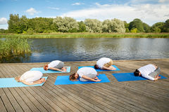 Group of people making yoga exercises outdoors Royalty Free Stock Images