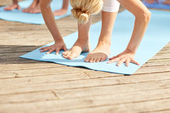 Group of people making yoga exercises outdoors Stock Image