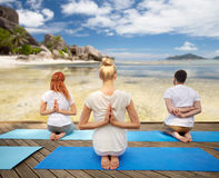 Group of people making yoga exercises over beach Royalty Free Stock Photos