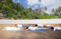 Group of people making yoga exercises over beach Stock Photos