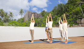 Group of people making yoga exercises over beach Stock Images
