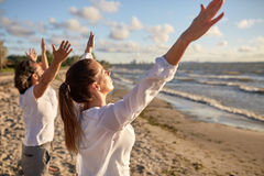 Group of people making yoga or meditating on beach Royalty Free Stock Image