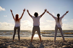 Group of people making yoga or meditating on beach Stock Photos