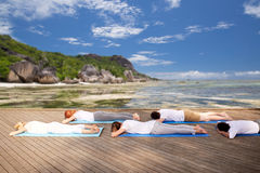 Group of people making yoga outdoors and lying. Fitness, yoga and sport concept - group of people lying on mats over exotic tropical beach Stock Photography
