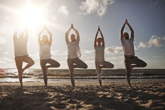 Group of people making yoga in tree pose on beach. Yoga, fitness, sport and healthy lifestyle concept - group of people in tree pose on beach stock photo