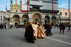 Group of people with masks on San Marco square during Venetian carnival. Stock Photos
