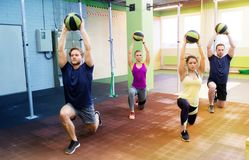 Group of people with medicine ball training in gym. Fitness, sport and exercising concept - group of people with medicine balls training in gym Stock Photography