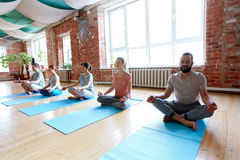 Group of people meditating at yoga studio. Fitness, yoga and healthy lifestyle concept - group of people meditating in lotus pose at studio Stock Photos