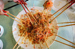 A group of people mixing and tossing Yee Sang dish with chop sticks. Stock Photography