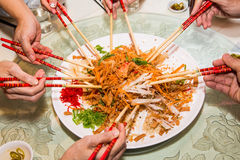 A group of people mixing and tossing Yee Sang dish with chop sticks. Yee Sang is a popular delicacy taken during Chinese New royalty free stock photo