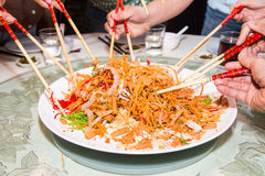 A group of people mixing and tossing Yee Sang dish with chop sticks. Yee Sang is a popular delicacy taken during Chinese New Year, Royalty Free Stock Photo