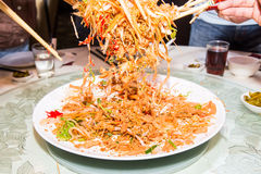 A group of people mixing and tossing Yee Sang dish with chop sticks. Yee Sang is a popular delicacy taken during Chinese New. Year, believed to bring good