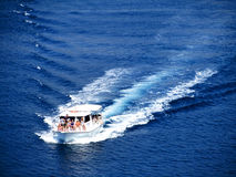 Group of people in a motor boat at sea. Budva, Montenegro - July 07, 2010: A group of people in summer clothes in a white motor boat at sea going fast. Motor stock photo
