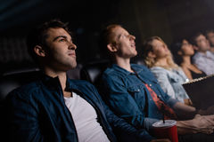 Group of people in multiplex theater. Young men with friends watching movie in cinema. Group of people in multiplex theater Royalty Free Stock Photos