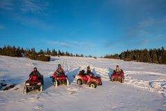 Group of people on off-road quad bikes in the the mountains in winter evening. Group of people sitting on off-road quad bikes in the the mountains in winter Stock Photo