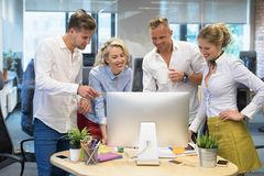 Group of people in office looking at computer. And enjoying successful results Royalty Free Stock Photos