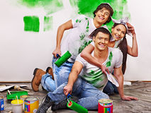 Group people paint wall at home. Royalty Free Stock Photos