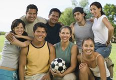 Group of people in park with woman holding soccer ball. stock image