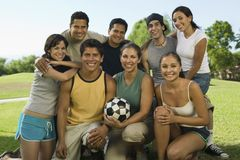 Group of people in park with woman holding soccer ball. stock photos