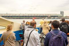 Group of people on passenger ferry heading towards the central station in Amsterdam, Netherlands royalty free stock photo