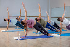 Group of people performing yoga. In gym Stock Image