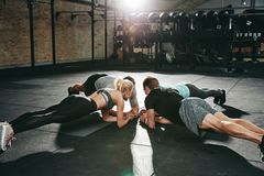 Group of people planking during a gym workout class. Group of fit young people in sportswear planking together on the floor of a gym during an exercise class royalty free stock images
