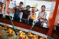 Group of people playing fishing game at amusement park Royalty Free Stock Photos