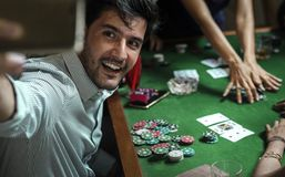 Group of people playing gamble in casino and taking selfie.  Stock Photos