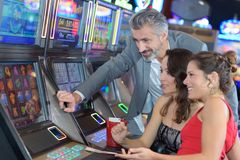 Group people playing at slot in casino. Group of people playing at a slot in a casino Royalty Free Stock Photo