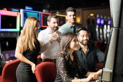 Group of people playing in slot machine. Pretty young women and a group of friends watching her play in a slot machine while she wins some money Stock Photos