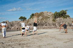 Group of people practice Capoeira on beach. Royalty Free Stock Image