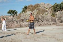 Group of people practice Capoeira on beach. Stock Photos
