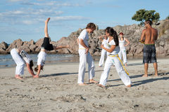 Group of people practice Capoeira on beach. Stock Photo