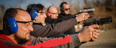 Group of people practice gun shoot on target on outdoor shooting range stock photography