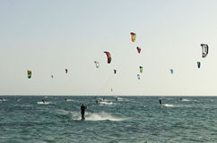 Group of people practicing kitesurf. A group of people practicing or competing in kiteboarding and kitesurf Royalty Free Stock Images