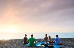 Group of people practicing morning meditation, yoga outdoors at sunrise on the beach. Feeling so comfortable and relax. Group of people practicing morning stock photos