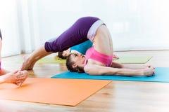 Group of people practicing yoga at home. Halasana pose. Royalty Free Stock Photography