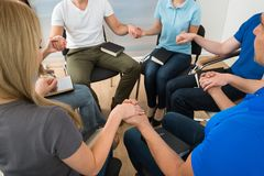 Group of people praying. Close-up Of People Holding Each Others Hand Praying Together Stock Photography