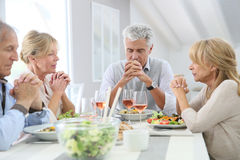 Group of people praying before dinner Royalty Free Stock Image
