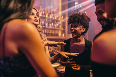 Group of people in the pub. Having fun. Young girls enjoying a night in club Royalty Free Stock Photos