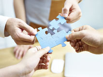 Group of people putting jigsaw pieces together Stock Photography