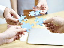 Group of people putting jigsaw pieces together Stock Photo